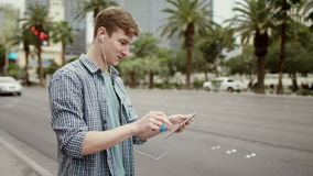 Videochat on a sidewalk in Vegas. Young man is standing on a sidewalk and having a video chat with his friends by using his tablet pc stock video