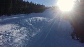 Videoclip des Leuteski fahrens und die Vierpersonenskisesselbahn, die die Bäume durchläuft, up einen Berg mit einem blauen Himmel stock footage