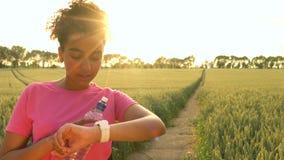 videoclip 4K do corredor fêmea da jovem mulher do adolescente afro-americano saudável bonito da menina da raça misturada que usa  filme