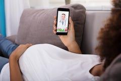 Videoconferência da mulher gravida com doutor On Smartphone imagens de stock