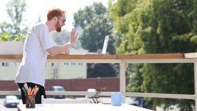 Videoconferência no portátil, bate-papo do homem novo, estando no balcão exterior Imagens de Stock Royalty Free