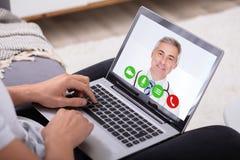 Videoconfer?ncia do homem com doutor On Laptop imagens de stock royalty free