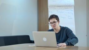 Videoconferencing för ung man med handleder på bärbara datorn i grupprum royaltyfria foton