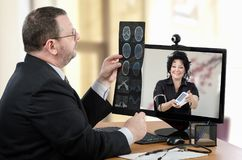 Videoconferencing with virtual doctor. Virtual male doctor uses videoconferencing to communicate with remote patient. Man goes over brain x-rays image in front royalty free stock photos