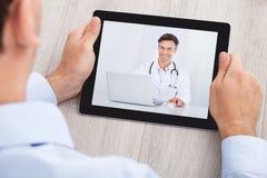 Videoconferência do homem de negócios com o doutor na tabuleta digital Foto de Stock