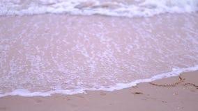 Videodielengte van woord '2018 'op een zandig strand die wordt geschreven door de tegemoetkomende golf worden gewassen stock footage