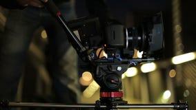 Videodslrcamera op schuif met lichten vooruitgaan en een omheining die op achtergrond achter de schermen videoproductie stock video