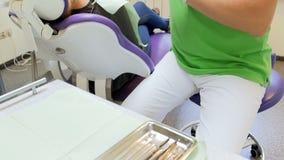 Videoen för closeupen 4k av tandläkaren i skyddande handskar tar det sterila instrumentet från metallmagasinet lager videofilmer
