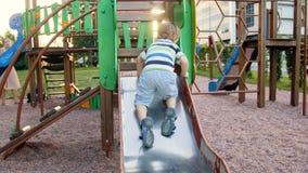 videoen 4k av den lilla litet barnpojkeklättringen på metallglidbana på lekplats på parkerar stock video
