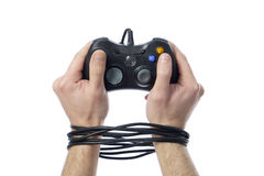 Videogame addiction. Hands tied up by a joypad meaning videogame addiction Stock Image