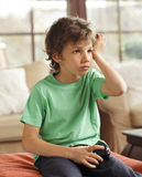 Videogame can be injurious to the health. Boy has a headache because of the too many videogame Royalty Free Stock Images