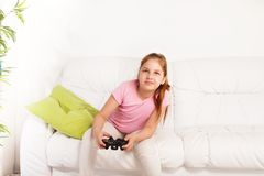 Videogame. Cute schoolgirl with intense expression playing videogame sitting on the sofa in living room Royalty Free Stock Photography
