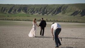Videograph die video met steadicam schieten De jonge mooie bruid in een huwelijkskleding gaat naar de bruidegom Vergadering van stock video