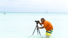Videographer on assignment on a tropical beach Royalty Free Stock Photo