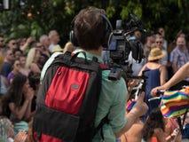 Videographer che lavora l'impianto di perforazione all'aperto mic della videocamera di evento della folla di contaminazione fotografie stock