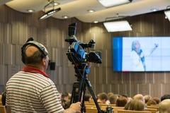 Videographer fa la radiodiffusione online alla conferenza Immagini Stock