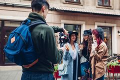 Videographer filmandemodeller på stadsgatan Man genom att använda steadicam och kameran för att göra längd i fot räknat Video for royaltyfri fotografi