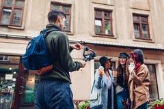 Videographer filmandemodeller på stadsgatan Man genom att använda steadicam och kameran för att göra längd i fot räknat Video for royaltyfri foto