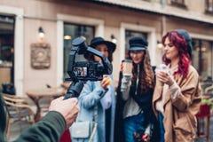 Videographer filmandemodeller p? stadsgatan Man genom att anv?nda steadicam och kameran f?r att g?ra l?ngd i fot r?knat Video for royaltyfria bilder