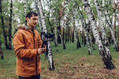 Videographer filming spring forest. Man using steadicam and camera to make footage. Video shoot. Digital devices for video shoot royalty free stock image