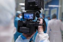 Videographer, habillé dans des vêtements blancs stériles, enregistre ce qui se produit dans le laboratoire médical photographie stock libre de droits
