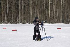 Videographer in the Park. Editorial image. the area, a Man in warm clothes and boots takes off in a snow-covered Park. Russia Bere stock photo