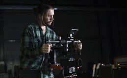 Videographer profissional que guarda a câmera na suspensão Cardan de 3 linhas centrais Videographer usando o steadicam O pro equi imagem de stock