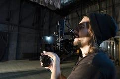 Videographer profissional usando a câmara de vídeo digital do cinema para filmar uma vídeo clip fotos de stock royalty free