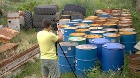 Videographer quita los viejos barriles de petróleo sucios Usando el trípode almacen de video