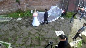 Videographer-Schießen-Hochzeitspaare an der alten Kirchennähe stock video