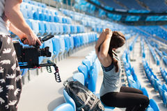 The videographer shoots on a professional camera like a sporty girl warming up, sitting in the stadium stock images