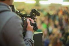 Videographer toma a una muchedumbre de gente en el pasillo Fotos de archivo