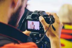 Videographer-Trieb mit einem DigitalkameraGeschäftstreffen Lizenzfreies Stockbild