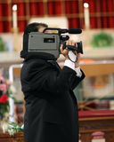 Videographer at Wedding. Videographer shooting video at church wedding Royalty Free Stock Photography