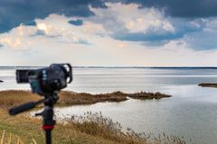 Videography from camcorder shooting nature. Videography from camcorder on tripod shooting cloudy sky over wild lagoon in winter royalty free stock photo
