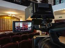 Videography in the interior. Digital video camera with LCD display. Led on-camera light.  Royalty Free Stock Image