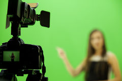 Videography. Video camera with the blurry lady Royalty Free Stock Image