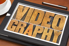 Videography word abstract in wood type. Videography word abstract - text in letterpress wood type on a digital tablet with a cup of tea royalty free stock images