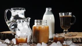 Videoimage dell'insieme delle bottiglie e dei vetri con latte, acqua, caffè nero e la bevanda del caramello Un cubo di ghiaccio s video d archivio