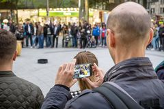 Videoing de photographie d'homme l'en public photo stock