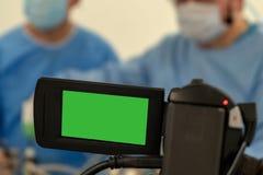 Videoinspelning och levande TV-sändning av arbetet av två kirurger Att fungera hyr rum det kirurgiska sjukhuset Grön skärmcamcord arkivbilder