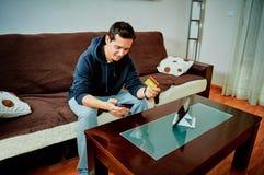 Videojuegos jovenes de la compra del muchacho sobre Internet con su tel?fono m?vil imagen de archivo