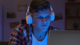 Videojugador adicto en los auriculares que sienten trastorno el soltar de la ronda en línea, ocio adolescente almacen de metraje de vídeo