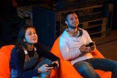Videojugador de dos jóvenes que se sienta en taburetes y que juega el togethe de los videojuegos Foto de archivo libre de regalías