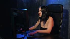 Videojugador de la muchacha en auriculares y con el ratón y el teclado en sus manos que juegan a los juegos de la red que se prep almacen de video