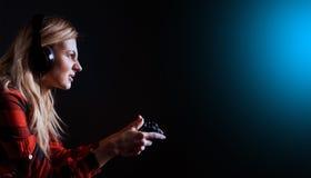 Videojugador de la muchacha en auriculares y con una palanca de mando que juega entusiasta en la consola imágenes de archivo libres de regalías