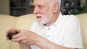 Videojugador del hombre mayor que juega a los videojuegos en casa Personas mayores modernas activas almacen de metraje de vídeo