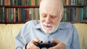 Videojugador del hombre mayor que juega a los videojuegos en casa Personas mayores modernas activas Estantes en fondo almacen de metraje de vídeo
