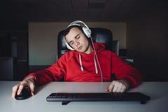 Videojugador dormido en casa en el ordenador Hombre joven que duerme en casa jugando Foto de archivo