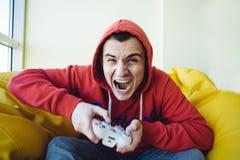 Videojugador emocional que se sienta en el sofá y que juega a los videojuegos usando un gamepad Vista enfocada de la cámara Fotos de archivo libres de regalías